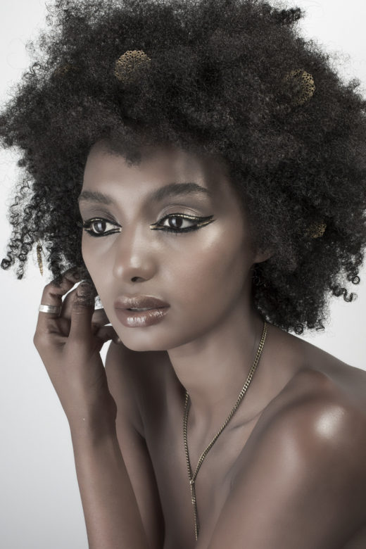 Gold eyeliner beauty shot on black skin model